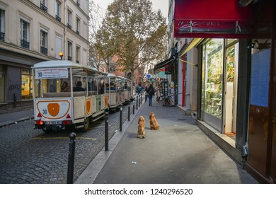 Paris / France - October 22 2018: Tourist train in the famous Montmartre district, with the brick and ceramic tile-faced façade of the Church of Saint-Jean-the-Montmartre in the background in autumn
