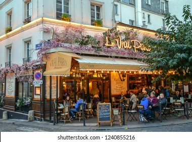 Paris / France - October 22 2018: People having aperitif sitting outdoor in a typical Parisian bistro in the Montmartre district