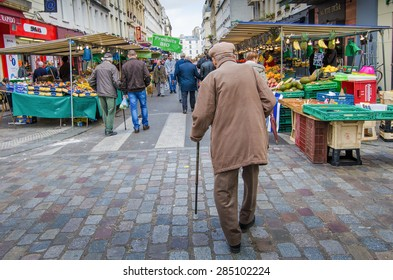 PARIS, FRANCE - OCTOBER 23, 2014: An old man with a cane walks among vegetable and fruits stands in the historic Marche d' Aligre.