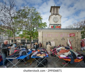 PARIS, FRANCE - OCTOBER 23, 2014: A man checks out a pair of pants through a pile of clothing at the popular flea market at the historic Place d' Aligre in the Bastille district.
