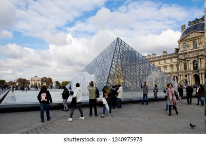 PARIS, FRANCE - OCTOBER 27 2018: people posing in front of the entrance of  The  Louvre under the crystal pyramid
