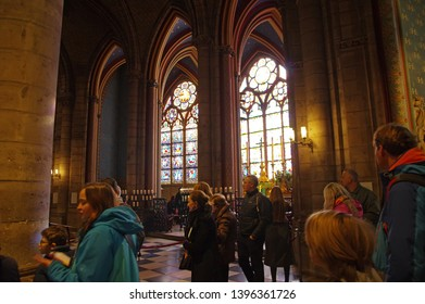 PARIS, FRANCE - OCTOBER 27 2018: People under stained Glass Windows in the famous Notre Dame de Paris, Gothic Interior of the Cathedral example of Rayonnant architecture