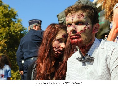 PARIS, FRANCE - OCTOBER 3, 2015: Zombie couple participating in Zombie parade at Place de la Republique and police force keeping order at background. Zombie Walk is an annual event in Paris.