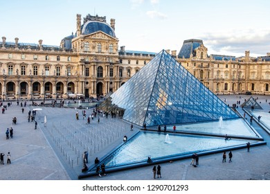 PARIS FRANCE - OCTOBER 3, 2018: Louvre museum at sunset. Magenta look in the horizont. Tourists walking in the square. Soft clouds in the sky