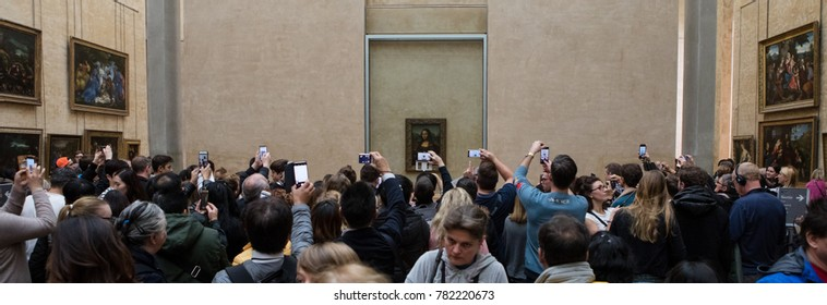 "Paris, France - October 30, 2017: Visitors take photos of Leonardo DaVinci's ""Mona Lisa (La Gioconda)"" at the Louvre Museum."