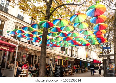 PARIS, FRANCE - OCTOBER 4, 2014: Parisian urban scene in Marais quarter. Locals and tourists relaxing at typical cafe terraces. Street decorated with hanging multicolored umbrellas.