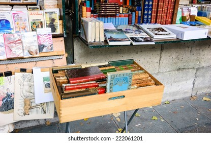 PARIS, FRANCE - OCTOBER 4, 2014: Bouquiniste stands over Seine river near Notre Dame cathedral. Selling books on the banks of the Seine began around the 16th century.