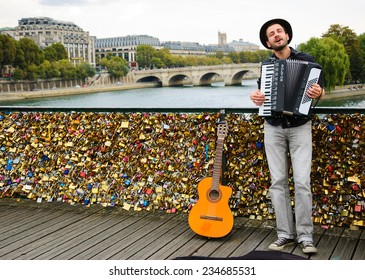 PARIS, FRANCE - OCTOBER 4, 2014: Unidentified young musician plays accordion on the Love Locks bridge . Dozens buskers perform on the streets and in the metro of Paris.