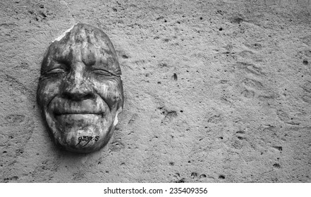 PARIS, FRANCE - OCTOBER 4, 2014: Happy face mask at wall near Tuileries Garden. Gregos creates replicas of his face with different expressions and install them on walls all over the world.