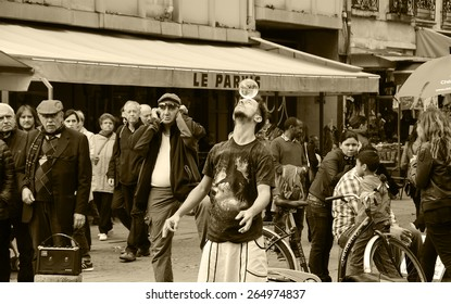 PARIS, FRANCE - OCTOBER 5, 2014: Unidentified young juggler with crystal ball on his head shows his art  to public near Pompidou Centre. Most of Parisian street artists perform in tourist hot spots.