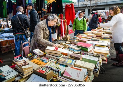 PARIS, FRANCE - OCTOBER 5, 2014: Women check the table of used books at a flea market in the historic Marche d' Aligre in the Bastille district.