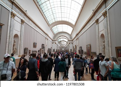 PARIS, FRANCE - OCTOBER 7 2018 - Louvre museum crowded of tourist taking pictures of painting and statue on first sunday of each month entrance is free