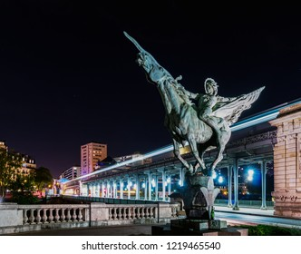Paris, France - October 8, 2018: France Reborn Statue on Pont de Bir-Hakeim at night with metro in background.