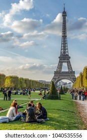 "PARIS, FRANCE, OCTOBER 9, 2015: Eiffel Tower and Champ de Mars in Paris. The World Heritage Site ""Banks of the Seine"". A lot of tourists relax."