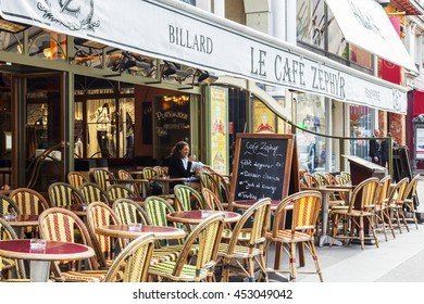 PARIS, FRANCE, on JULY 12, 2016. Typical city street. Little tables of outdoor cafe on the sidewalk.