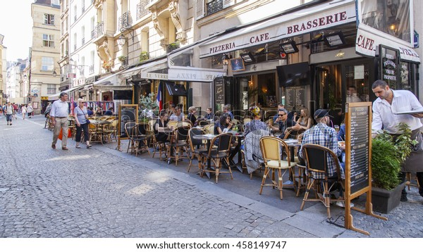 PARIS, FRANCE, on JULY 5, 2016. Typical Parisian street in the morning. People have a rest and eat in cafe under the open sky.