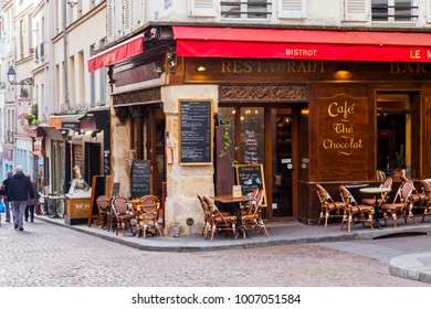 PARIS, FRANCE, on October 30, 2017. Little tables of traditional street cafe on crossing of two streets expect visitors in the morning