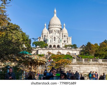 PARIS, FRANCE, on October 30, 2017. Numerous tourists walk and have a rest on a slope of Montmartre, at the bottom of the basilica Sakre Kerr which is one of city symbols