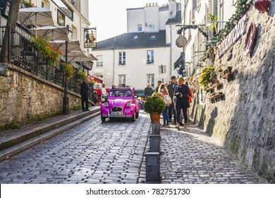 PARIS, FRANCE, on October 30, 2017. Autumn city landscape. Stylish beautiful houses make an architectural complex of the street on Montmartre. Pink a retro the car goes on the road