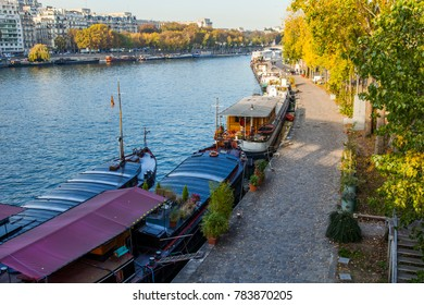 PARIS, FRANCE, on October 30, 2017. Autumn city landscape. The sunset sun lights the river Seine and its embankments. Manned barges are moored to the coast.