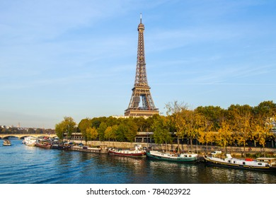 PARIS, FRANCE, on October 30, 2017. Autumn city landscape. The sunset sun lights the river Seine and its embankments. Manned barges are moored to the coast. Eiffel Tower in the distance