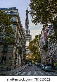 PARIS, FRANCE, on October 30, 2017. The sunset sun lights the city street and the Eiffel Tower in the distance. Numerous cars are parked near the sidewalk