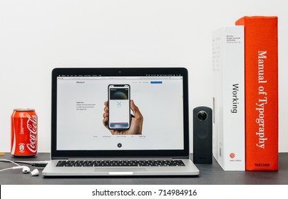 PARIS, FRANCE - SEP 13, 2017: Minimalist creative room table with Safari Browser open on MacBook Pro laptop showcasing Apple Computers website with latest iPhone X 10 with apple pay with Face ID