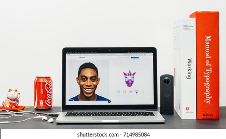 PARIS, FRANCE - SEP 13, 2017: Minimalist creative room table with Safari Browser open on MacBook Pro laptop showcasing Apple Computers website with latest iPhone X 10 with unicorn animoji