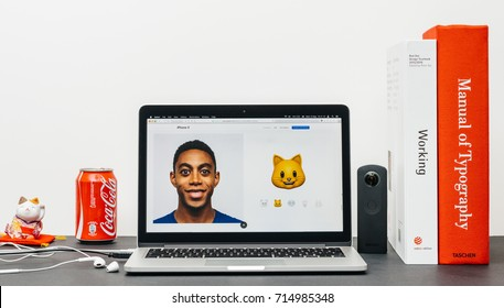 PARIS, FRANCE - SEP 13, 2017: Minimalist creative room table with Safari Browser open on MacBook Pro laptop showcasing Apple Computers website with latest iPhone X 10 with cat animoji emoji
