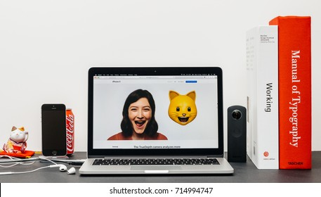 PARIS, FRANCE - SEP 13, 2017: Minimalist creative room table with Safari Browser open on MacBook Prolaptop showcasing Apple Computers website with latest iPhone X 10 with woman cat animoji emoji