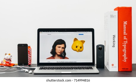 PARIS, FRANCE - SEP 13, 2017: Minimalist creative room table with Safari Browser open on MacBook Pro laptop showcasing Apple Computers website with latest iPhone X 10 with sad woman cat animoji