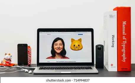 PARIS, FRANCE - SEP 13, 2017: Minimalist creative room table with Safari Browser open on MacBook Pro laptop showcasing Apple Computers website with latest iPhone X 10 with woman cat animoji emoji
