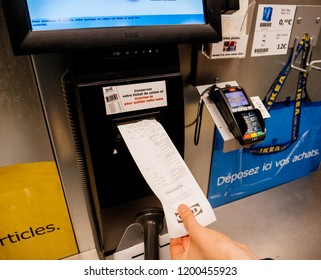 PARIS, FRANCE - SEP 2, 2017: Young woman taking receipt at the sef-service counter inthe IKEA furniture store scanning paying for products