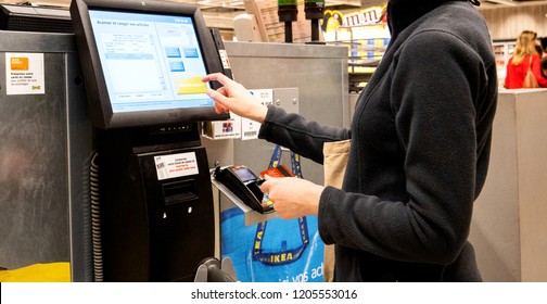 PARIS, FRANCE - SEP 2, 2017: Young woman paying at the sef-service counter inthe IKEA furniture store using the touchscreen display