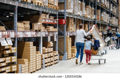PARIS, FRANCE - SEP 2, 2017: Rear view of young woman pushing cart inside large warehouse iof IKEA furniture store being accompanied by her kids - single mother concept