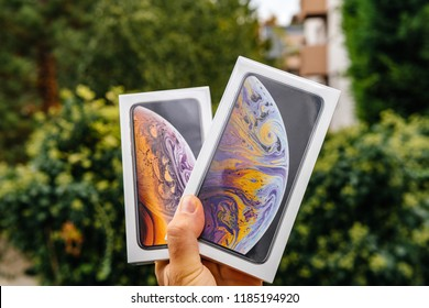 PARIS, FRANCE - SEP 21, 2018: Proud man customer POV comparing the new latest iPhone Xs and Xs Max smartphones telephones before the unboxing against green background