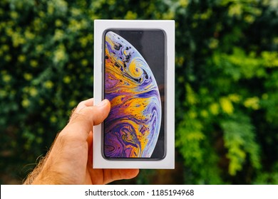 PARIS, FRANCE - SEP 21, 2018: Proud man customer POV comparing the new latest iPhone Xs Max smartphone telephone before the unboxing against green background