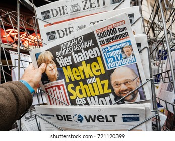 PARIS, FRANCE - SEP 23, 2017: Man buying latest newspaper Die Bild with with portrait of Angela Merkel And Martin Schulz before the election in Germany for the Chancellor of Germany