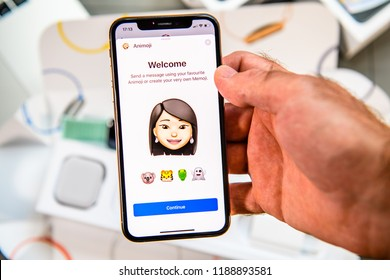 PARIS, FRANCE - SEP 24, 2018: Unboxing of iPhone Xs Max with demonstration of Messaging App with new Animoji Memoji features characters - augmented reality communication create very own asian ethncity