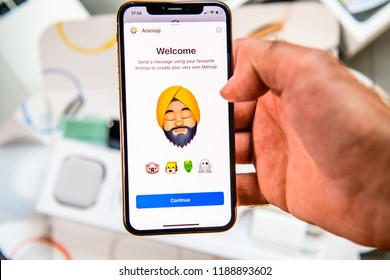 PARIS, FRANCE - SEP 24, 2018: Unboxing of iPhone Xs Max with demonstration of Messaging App with new Animoji Memoji features characters - augmented reality communication create very own indian male