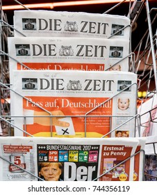 PARIS, FRANCE - SEP 25, 2017: International and German newspaper at press kiosk with portrait of Angela Merkel after election in Germany for Chancellor of Germany, the head of the federal government