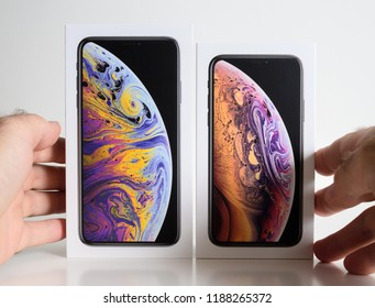 PARIS, FRANCE - SEP 25, 2018: New iPhone Xs and Xs Max cardboard box compare before unboxing of smartphone model by Apple Computers against white background - which one to choose decision