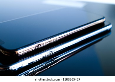 PARIS, FRANCE - SEP 25, 2018: One above another iPhone Xs and Xs Max smartphone model by Apple Computers close up of newest golden iPhone mobile phone device on technology blue reflective background