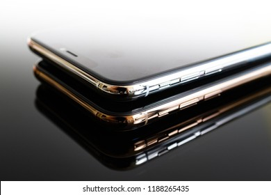 PARIS, FRANCE - SEP 25, 2018: One above another iPhone Xs and Xs Max smartphone model by Apple Computers close up of newest golden silver iPhone mobile phone device on gray reflective background