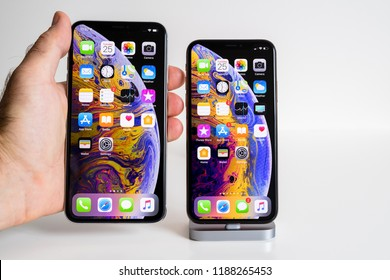 PARIS, FRANCE - SEP 25, 2018: Male hand compare new iPhone Xs 11 Pro and Xs Pro Max smartphone model by Apple Computers close up with hand holding the big Max one featuring multiple apps