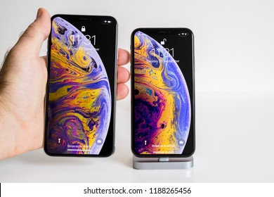 PARIS, FRANCE - SEP 25, 2018: Male hand compare new iPhone Xs and Xs Max smartphone model by Apple Computers close up with home screen before unlocking the device and liquid wallpaper