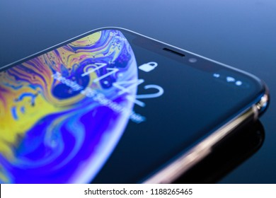 PARIS, FRANCE - SEP 25, 2018: Detail of the new iPhone Xs and Xs Max smartphone model by Apple Computers close up of golden Apple iPhone mobile phone device on reflective blue technology background