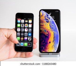 PARIS, FRANCE - SEP 25, 2018: Male hand compare new iPhone Xs and Xs Max smartphone model by Apple Computers close up with old iphone SE