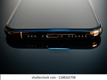 PARIS, FRANCE - SEP 25, 2018: New iPhone Xs and Xs Max smartphone model by Apple Computers close up of the newest golden Apple Iphone mobile phone device reflective background