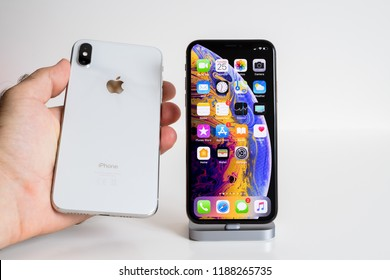 PARIS, FRANCE - SEP 25, 2018: Male hand compare new iPhone Xs and Xs Max smartphone model by Apple Computers close up with man holding the white one